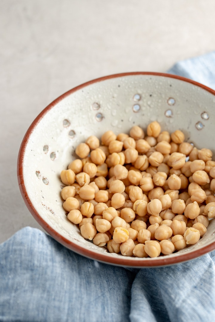 Close-up of chickpeas drained and rinsed in a stoneware colander.