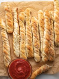 Homemade breadsticks with marinara sauce for dipping.