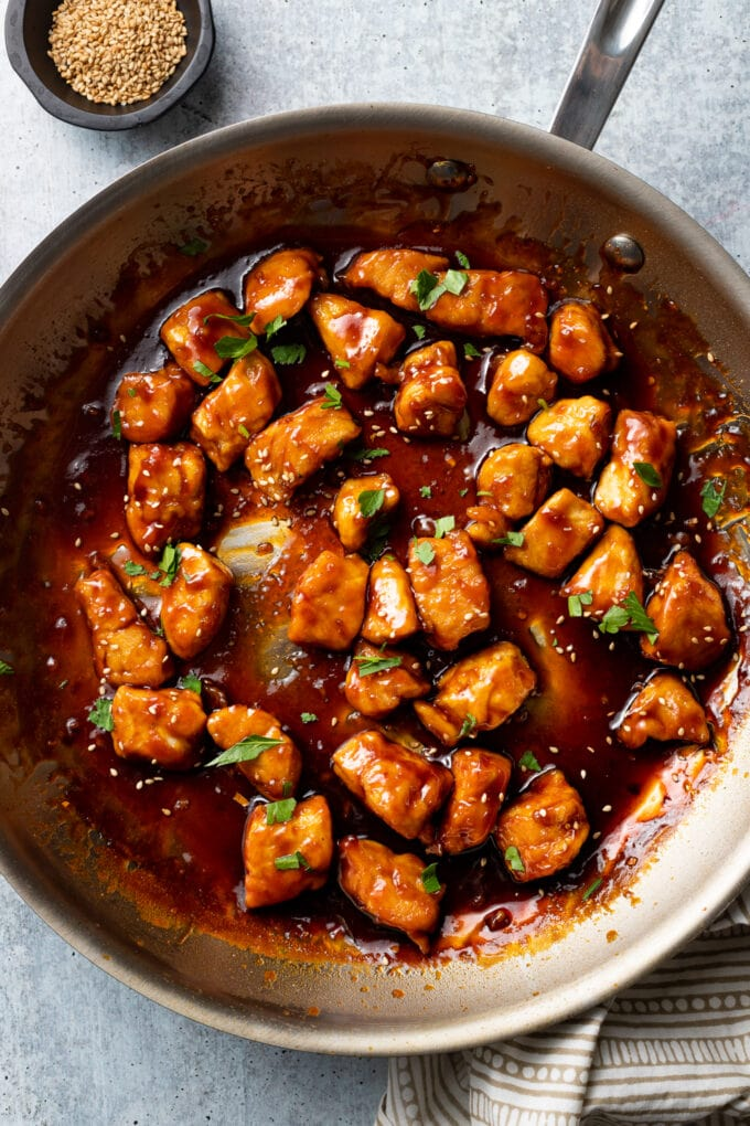 Close-up of bourbon chicken, cooked in a skillet.