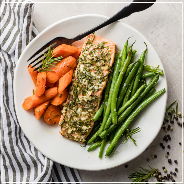 A plate of rosemary garlic salon with carrots and green beans.