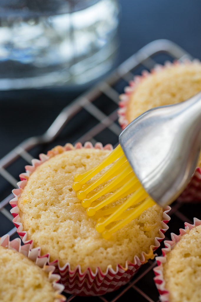 Using a pastry brush to brush tequila onto the tops of baked Paloma cupcakes.