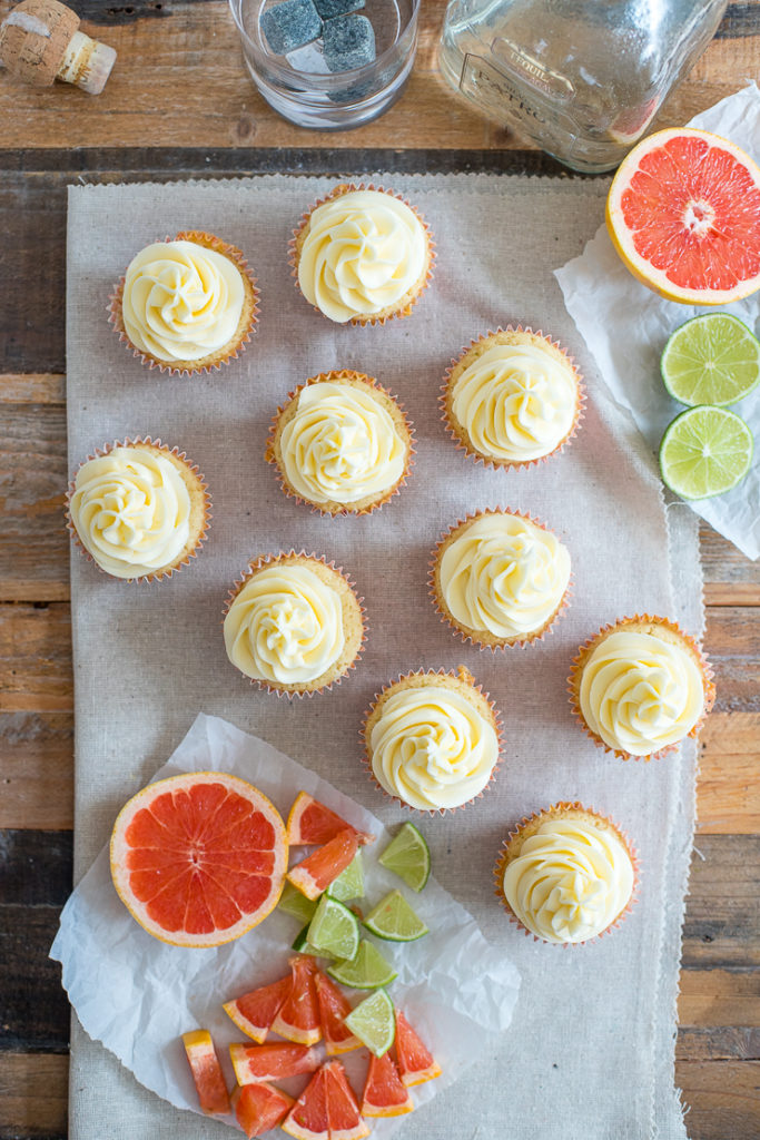 Flat-lay of Paloma cupcakes with grapefruit and lime wedges scattered around.
