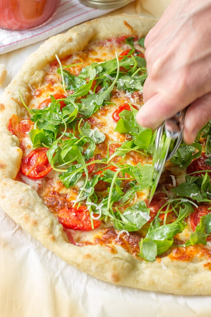 Pizza with marinara sauce, bacon, pan-roasted tomatoes, and fresh arugula. Fresh and delicious!