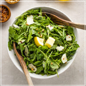 Bowl filled with quick and easy arugula Parmesan salad.