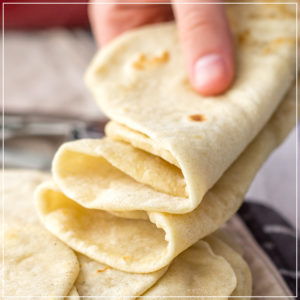 A hand holding a stack of soft, pliable homemade flour tortillas.