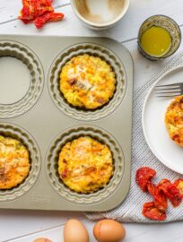 A pan of chorizo sun-dried tomato mini frittatas, surrounded by coffee, orange juice, and eggs.