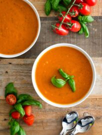 Two bowls of creamy roasted tomato basil soup, surrounded by spoons, fresh basil, and cherry tomatoes on the vine.