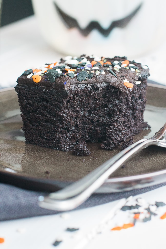 A slice of spooky blackout chocolate buttermilk cake with one forkful removed.