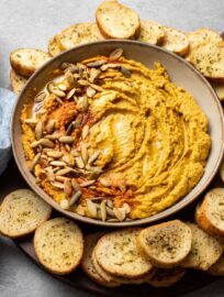 Bowl of pumpkin hummus with pumpkin seeds and paprika.