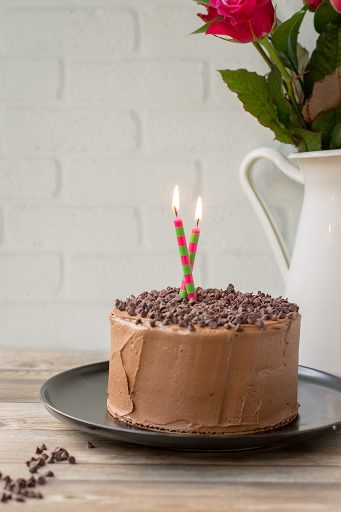 A tiny chocolate cake with mocha buttercream frosting and chocolate chips, with candles lit for a birthday.