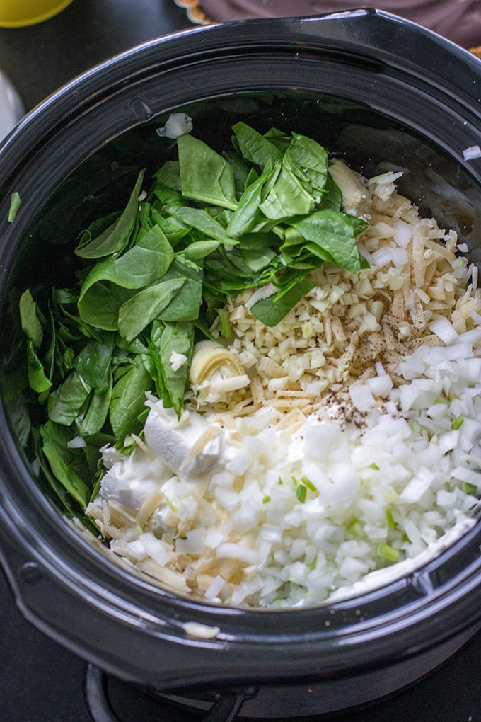 Spinach, artichokes, mozzarella, cream cheese, chopped onion, and seasonings, all in the crockpot and ready to go for a skinny spinach artichoke dip.