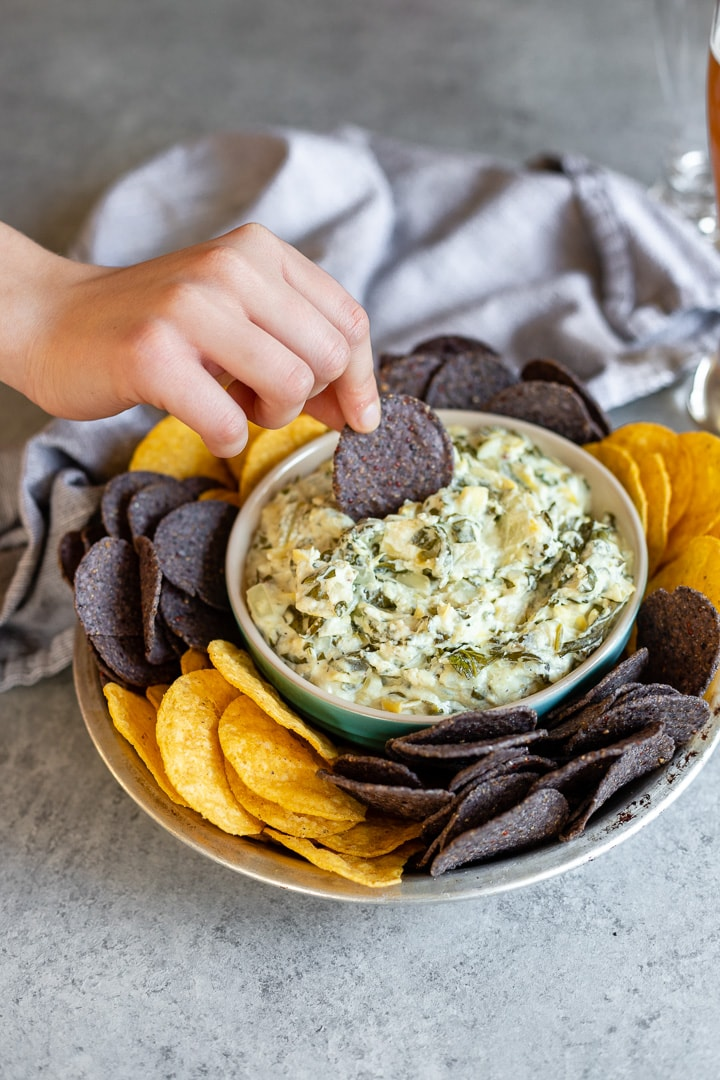 A hand dipping a blue tortilla chip into a bowl of piping hot spinach artichoke dip.
