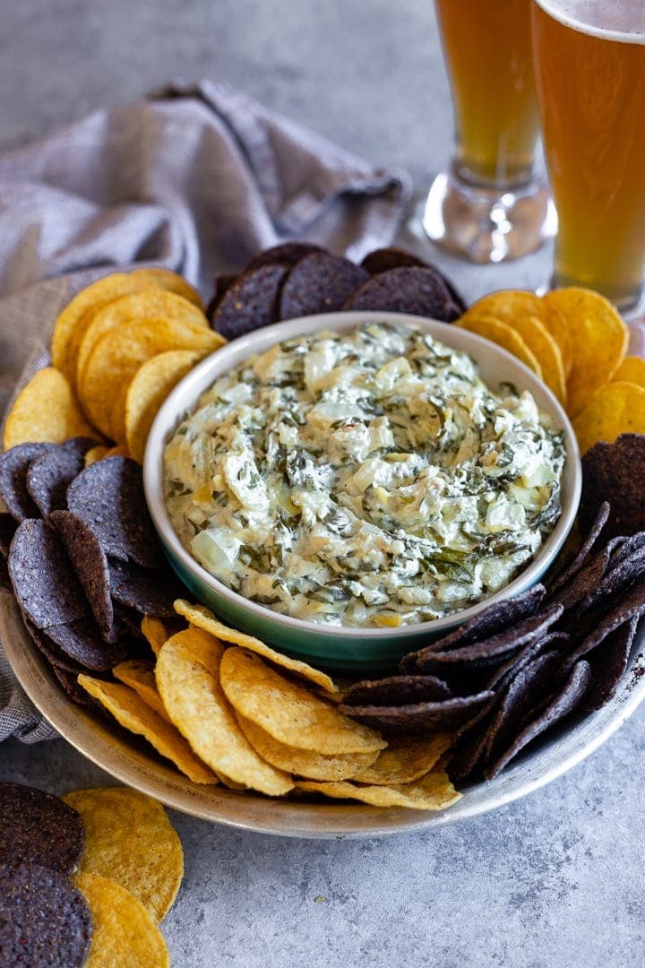 A bowl of skinny crockpot spinach artichoke dip served with tortilla chips and cold beer.