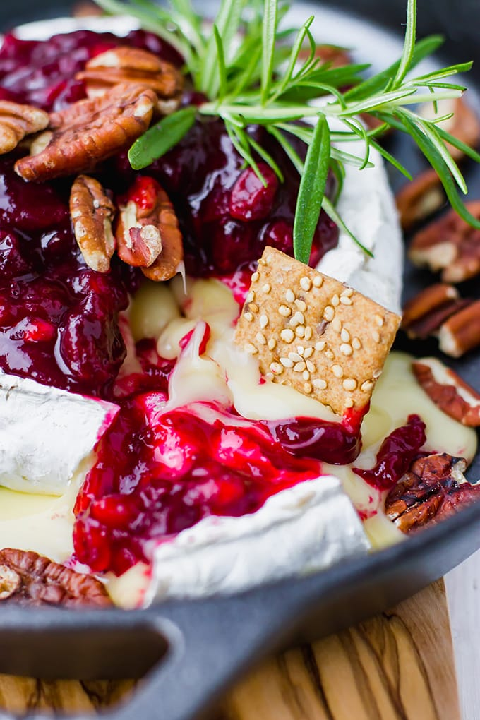 Close-up of a wedge of cranberry pomegranate baked brie with a cracker scooping out warm, melted cheese.