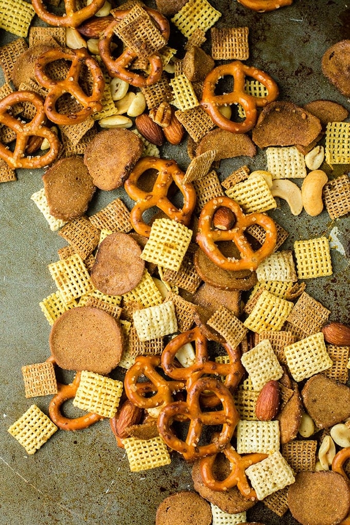 Rye chip Chex mix with pretzels and nuts spilling across a dark baking sheet.