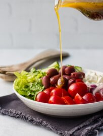 A stream of homemade Greek salad dressing being poured onto a Greek salad.