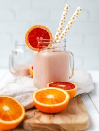 A bright pink blood orange banana smoothie, served in a mason jar with two straws.