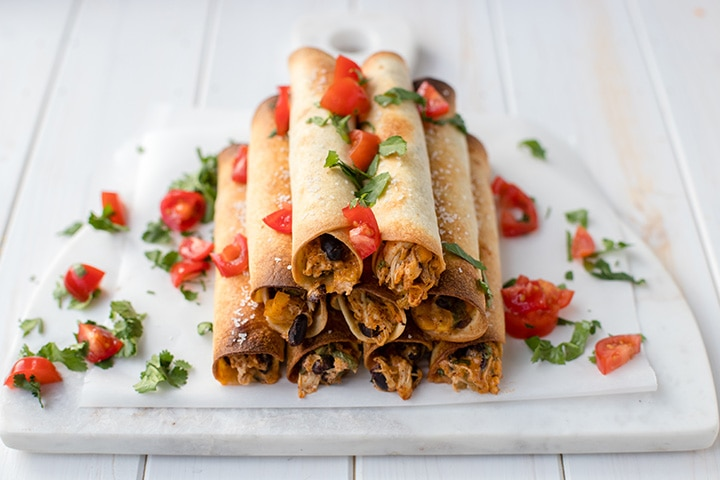A white tray filled with oven-baked chicken black bean taquitos.