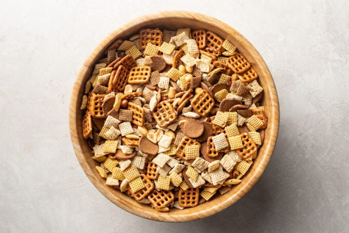 Wooden mixing bowl full of Chex mix.