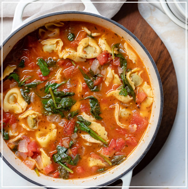 A white Dutch oven filled with hearty white bean tortellini soup with spinach and diced tomatoes.