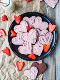Heart-shaped strawberry-frosted chocolate sugar cookies on a black plate, scattered with freshly-cut strawberries.