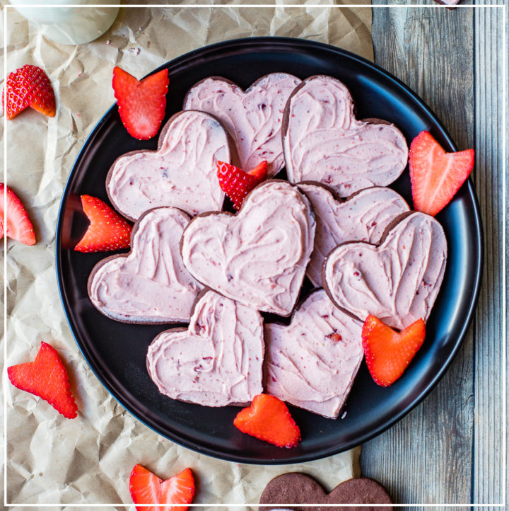A large pile of chocolate sugar cookies with strawberry frosting on a black plate with fresh strawberries cut to look like hearts.