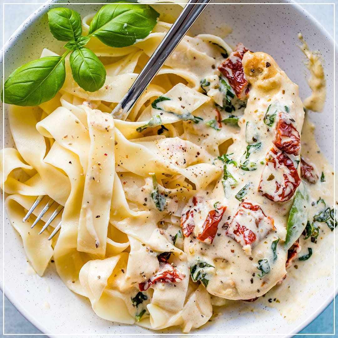 A bowl filled with pasta, creamy Tuscan chicken with spinach and sun-dried tomatoes, and a fresh basil garnish.