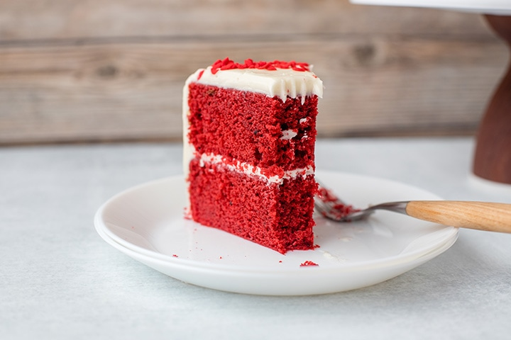 A slice of red velvet cake with cream cheese frosting.