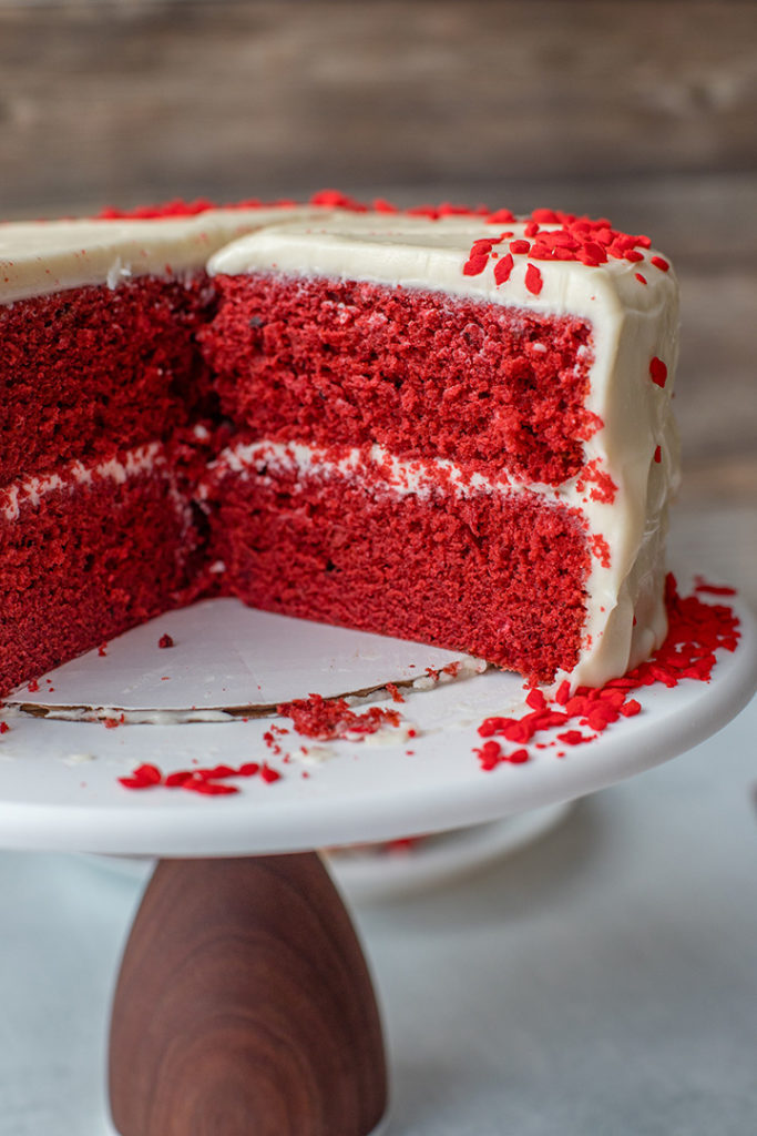 A cut open cross-section of red velvet layer cake.