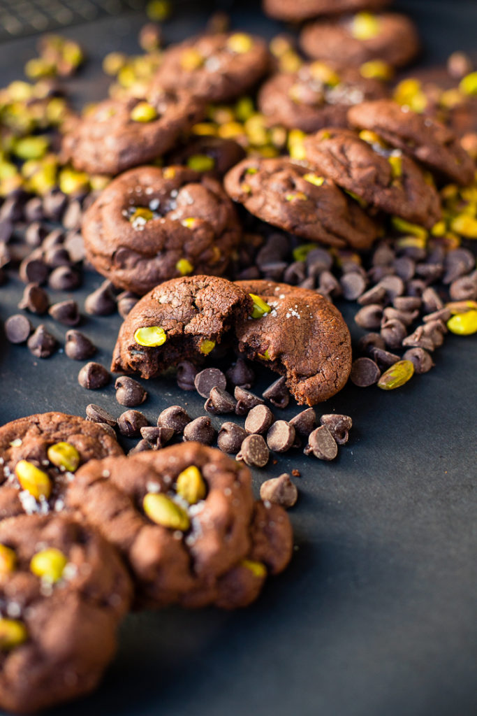 A pile of sea salt pistachio chocolate chip cookies, with one cookie broken apart.