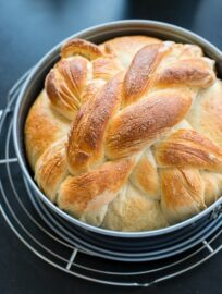A just-baked loaf of homemade paska, the traditional Slovak Easter bread, still in the pan and resting on a cooling rack.