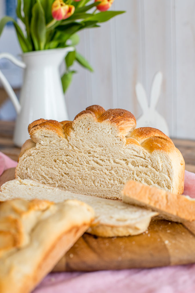 A cut-open loaf of paska, with slices arrayed in front, and a vase of flowers and decorative bunny in the background.