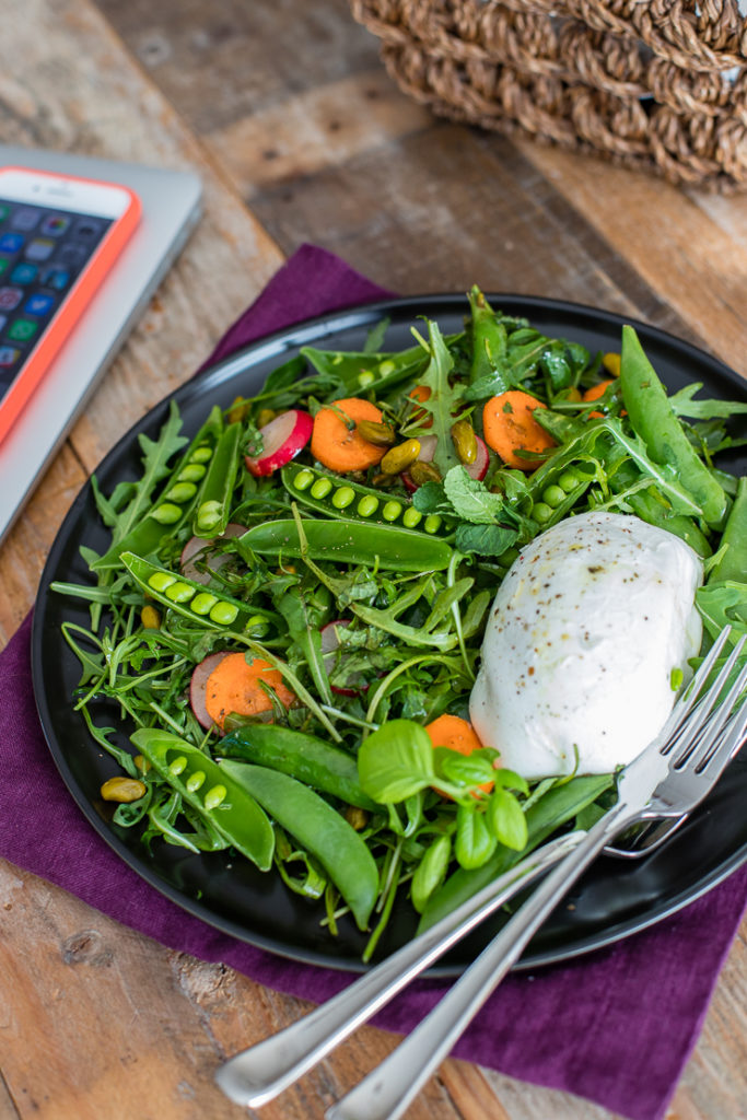 A working lunch with a healthy, fresh sugar snap pea salad with Buffalo mozzarella alongside a laptop and iPhone.