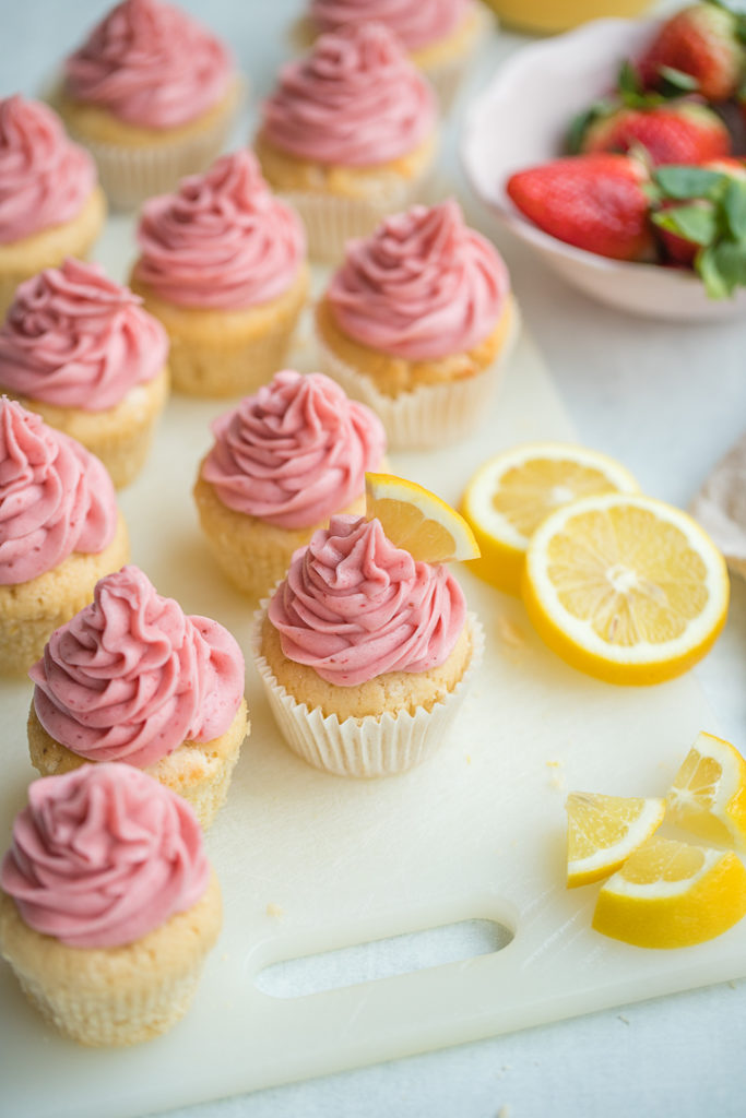 An array of strawberry lemonade cupcakes scattered next to fresh strawberries and cut lemon slices.