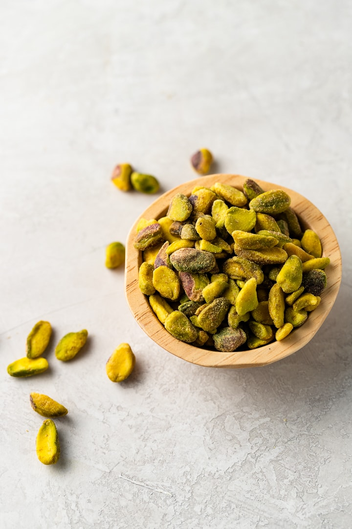 Close up image of shelled pistachios in a small wooden bowl.