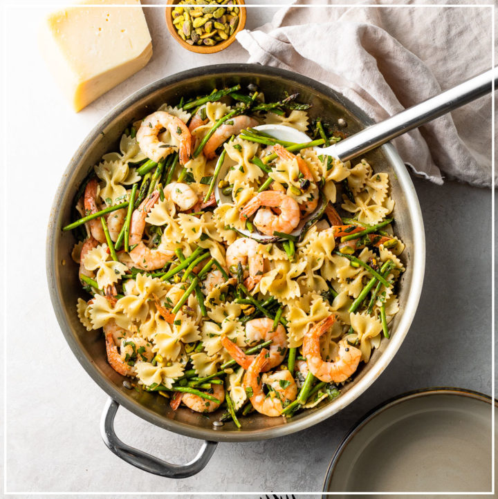 A large skillet filled with lemon asparagus pasta with shrimp and pistachios.