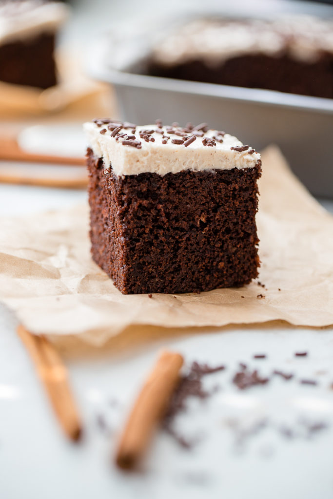 A small square slice of Mexican chocolate cake with cinnamon frosting and chocolate sprinkles, set on a piece of parchment paper.