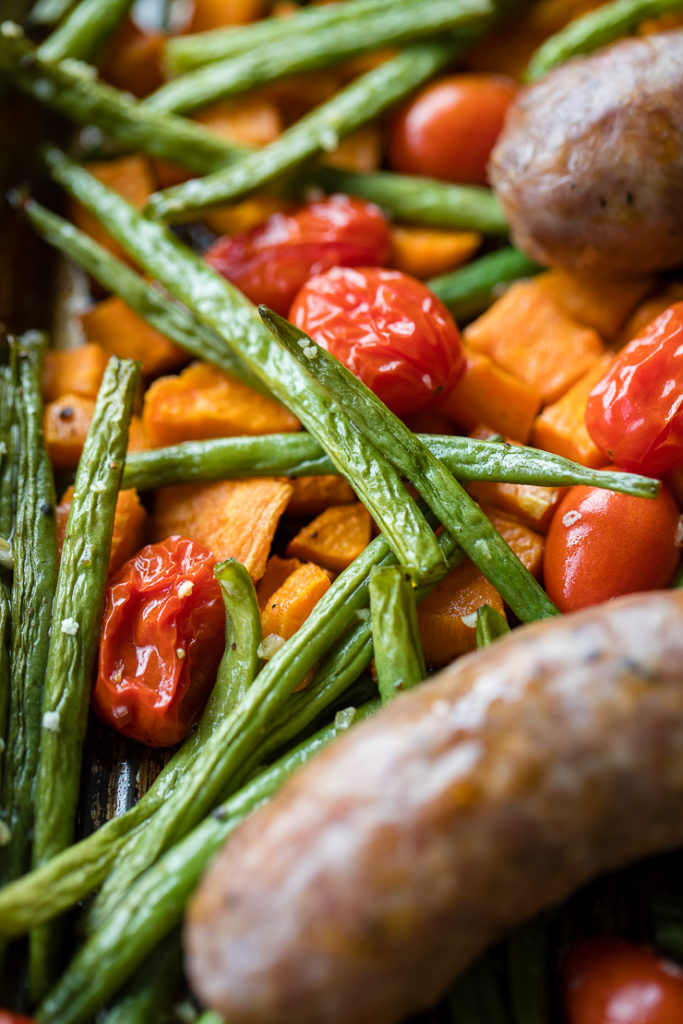Close-up of crinkly roasted green beans, cherry tomatoes, and sweet potatoes.