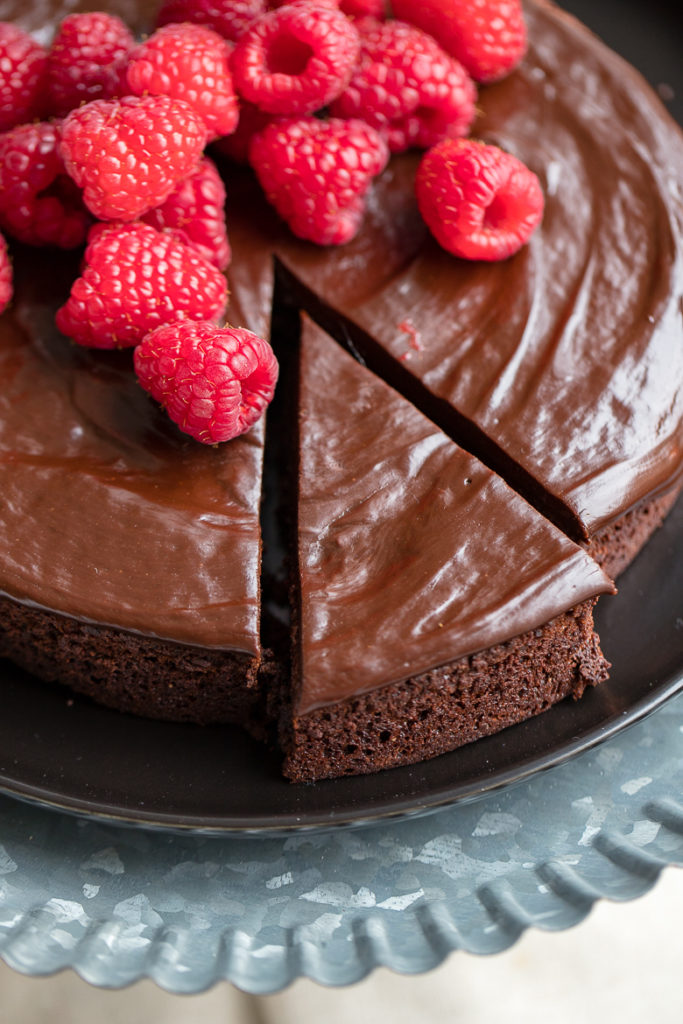 A just-cut slice of rich, perfect flourless chocolate cake with chocolate ganache and fresh raspberries.