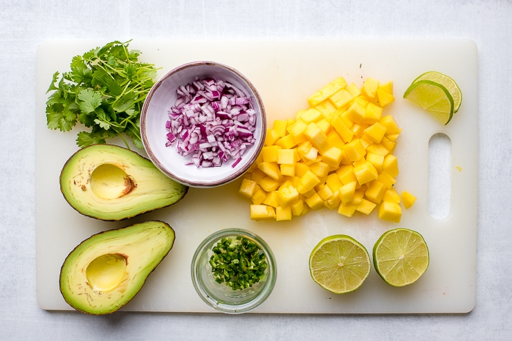 Ingredients for mango avocado salsa prepared and on a cutting board.