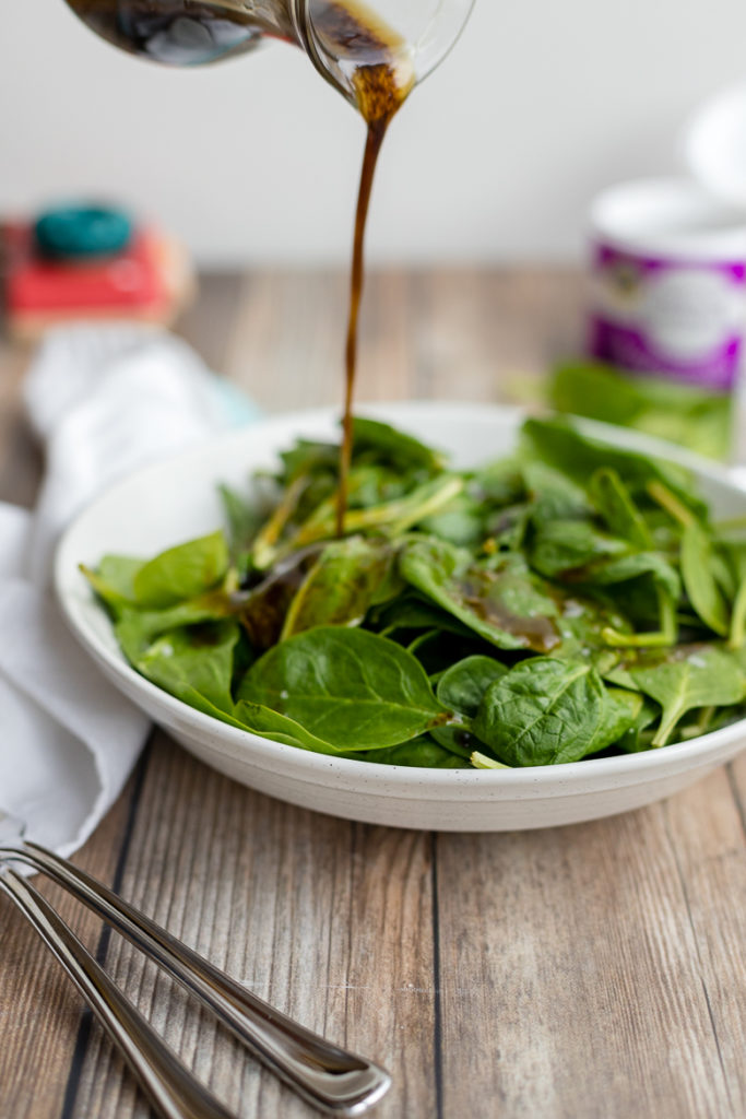 Pouring balsamic vinaigrette out of a cruet onto a simple spinach salad.