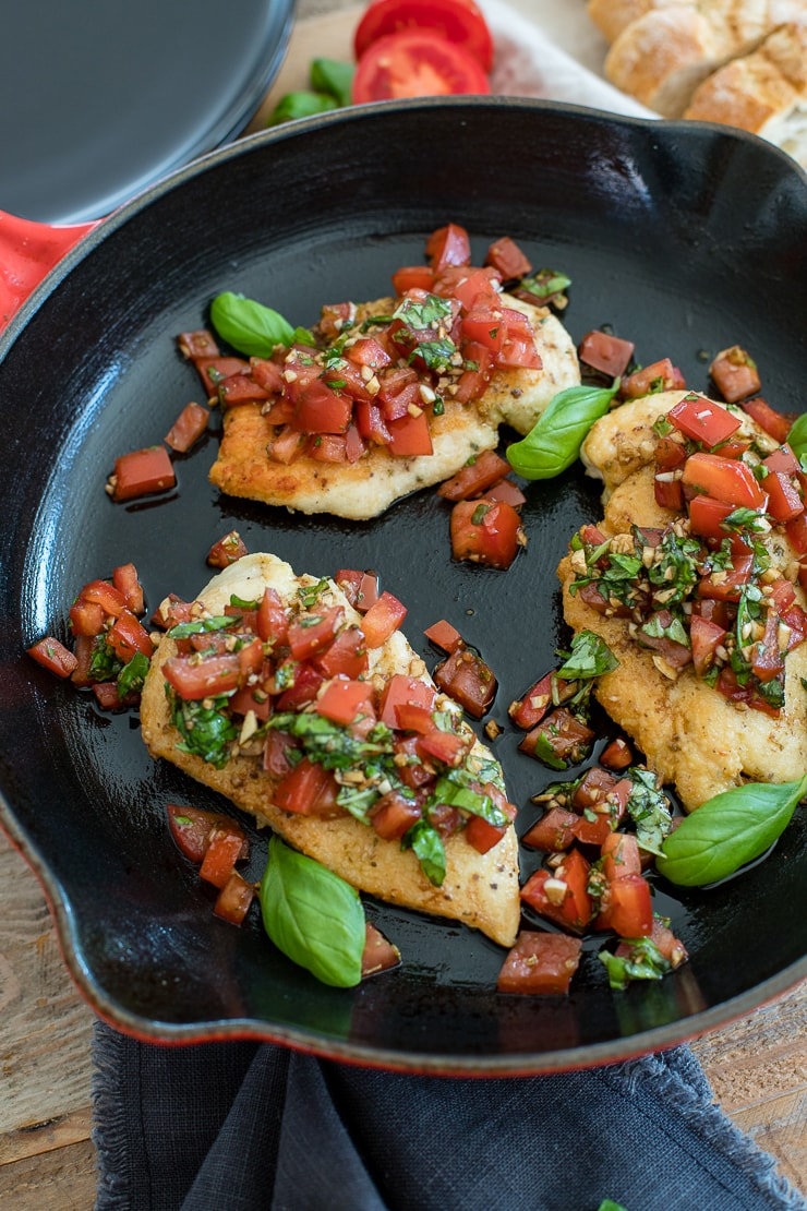 A Le Creuset cast iron pan filled with Italian herb bruschetta chicken, ready to serve.