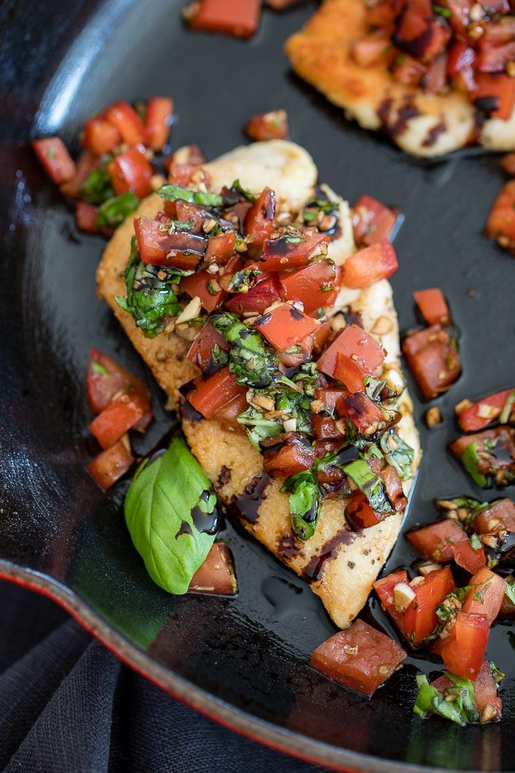 Close-up of Italian bruschetta chicken, dressed with fresh tomatoes, basil, and balsamic glaze.