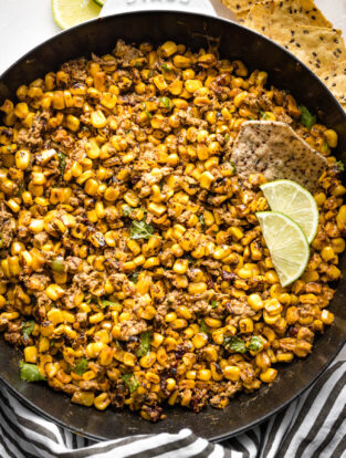 Skillet full of skinny chipotle street corn dip, served hot with tortilla chips.