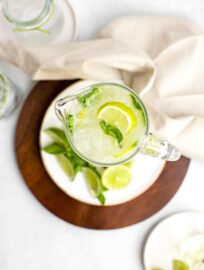 Overhead shot of a tall glass pitcher filled with sparkling limeade, garnished with lime wedges and mint.