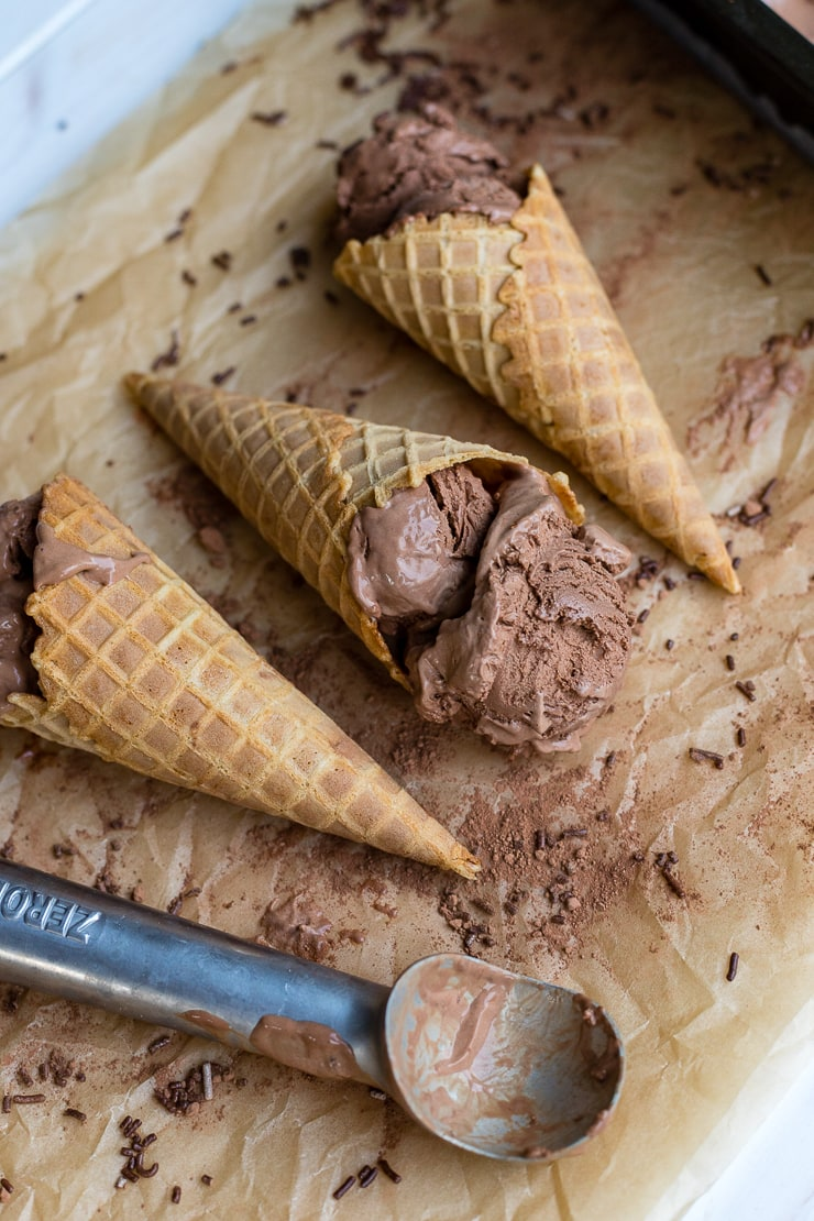 Three waffle cones filled with French style double chocolate ice cream, lying on parchment paper.