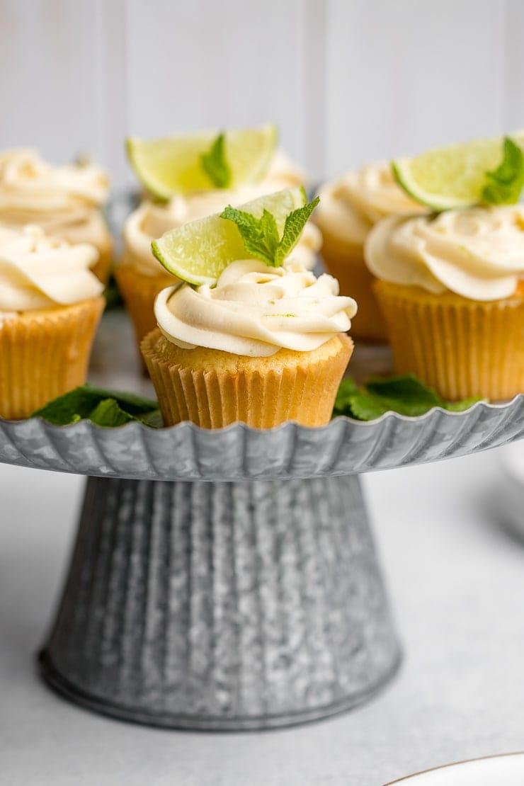 Spread of mojito cupcakes on a galvanized cake stand.