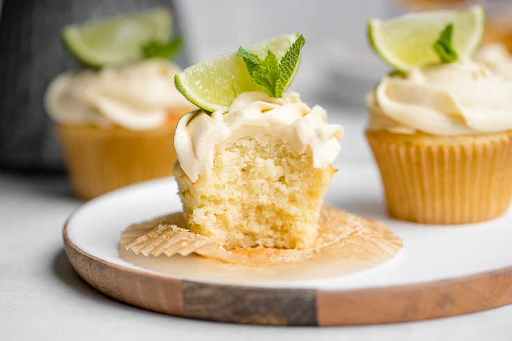 Mojito cupcake on a white plate with one bite removed.