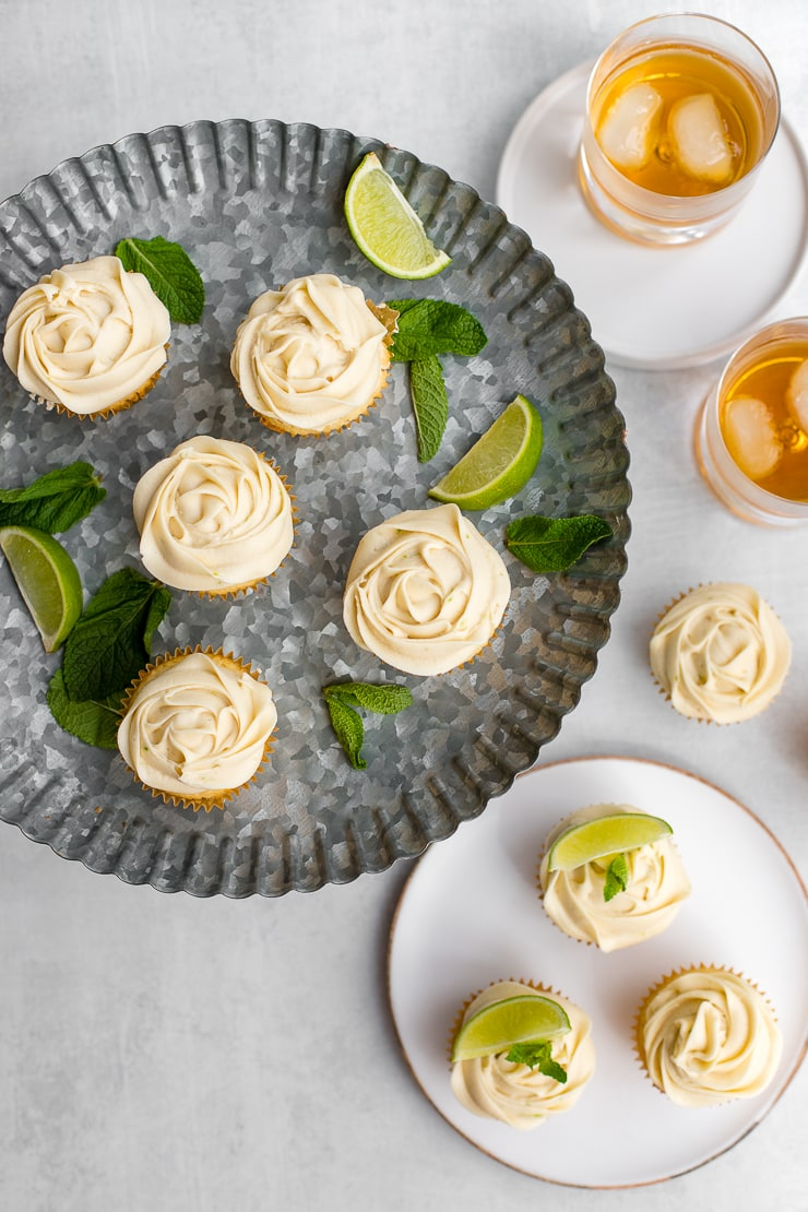 Flat-lay of mojito cupcakes arranged on a galvanized cake platter surrounded by more cupcakes and glasses of rum on the rocks.