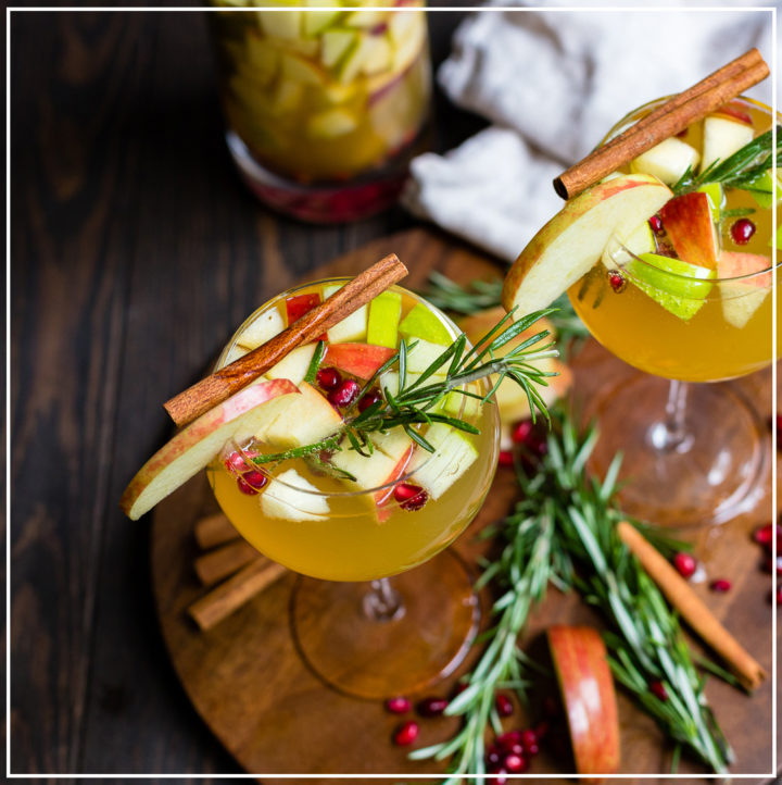 Two glasses of autumn harvest white sangria with apples and pears.